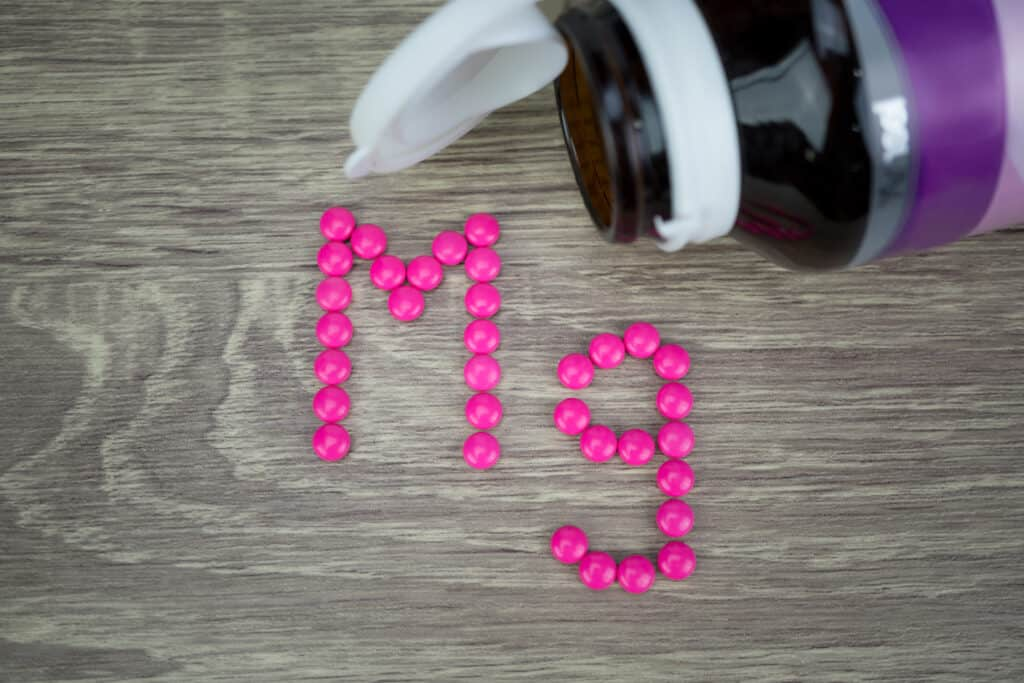 Pink pills forming shape to Mg alphabet on wood background